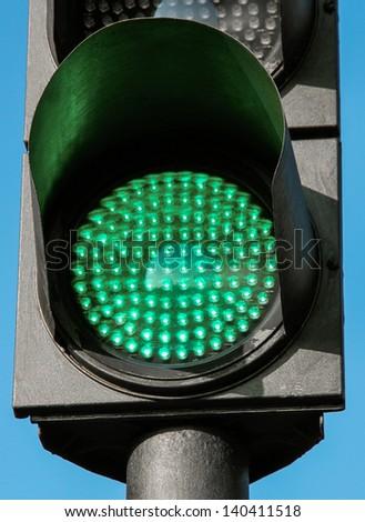 Traffic light in green light lit day - stock photo