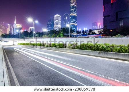 Traffic through downtown guangzhou with trail of lights - stock photo