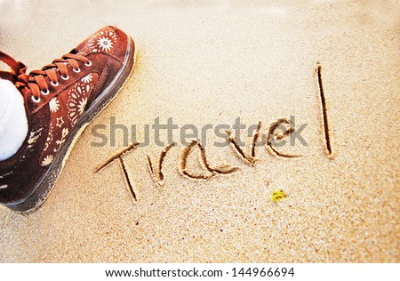 """travel"" written in sand beach - stock photo"