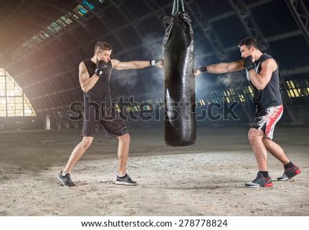 Two boxers hitting the sandbag  - stock photo