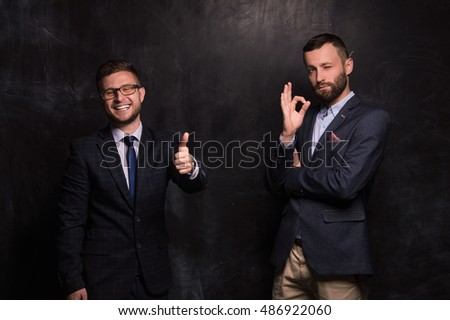 Two businessman standing on the background of the chalk board and convincing smile