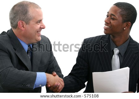 Two businessmen smiling and shaking hands. Shot in studio over white.