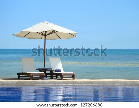 Two chairs and white umbrella on the beach - stock photo