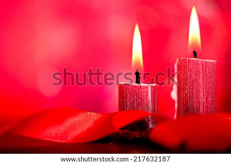 two christmas candles and red background