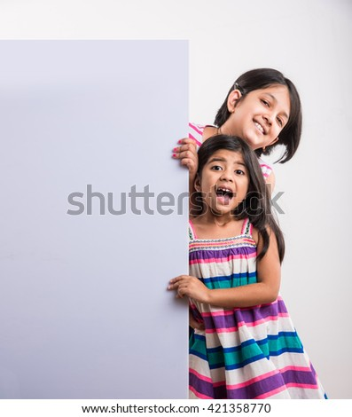 two cute Indian little girls presenting with a blank white board, little asian girls presenting white board with blank copy space - stock photo