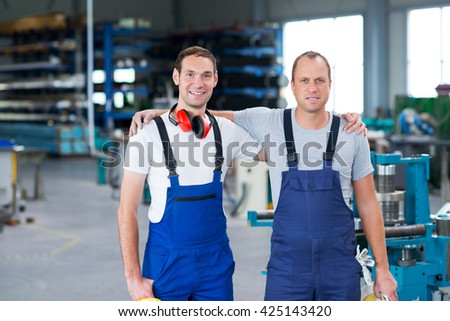 two friendly worker together in the factory - stock photo