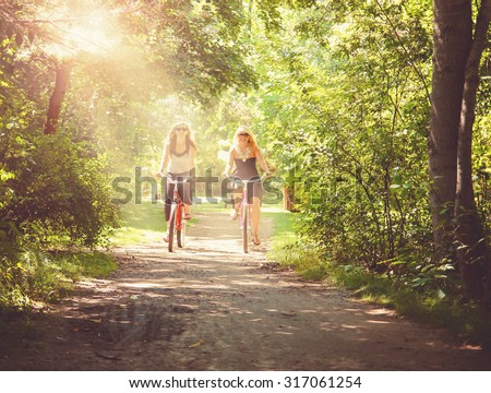 two girls riding bikes on a path in a park full of trees done with a retro vintage instagram filter app or action effect   - stock photo