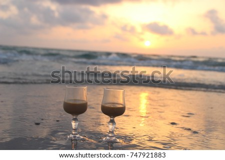 Two glasses on the beach. The beautiful morning sunrise at the sea.