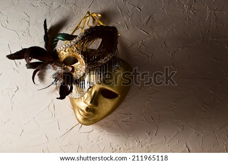 Two golden Venetian masks on  old wall