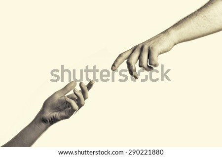 two hands reaching toward each other - stock photo
