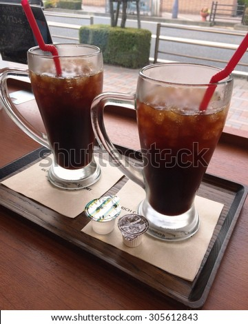 two ice black coffees on a woody table