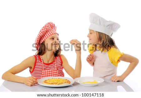 Two kids dressed as chefs preparing a pizza - isolated - stock photo
