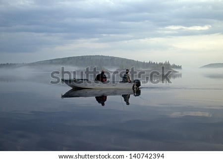 two men in a boat fishing on a calm lake - stock photo