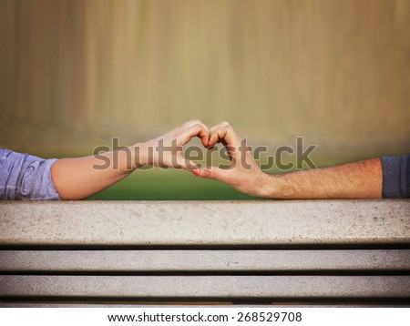two people making a heart shape with their hands on a bench toned with a retro vintage instagram filter app or action (shallow depth of field on the thumbs)  - stock photo