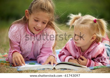 two schoolgirls is  reading  a big  book on the background of green meadows - stock photo