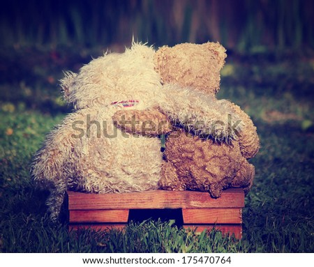 two teddy bears on a bench with arms around each other with a retro vintage instagram filter - stock photo