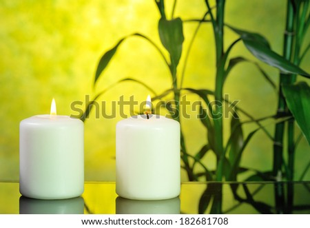 two white candles with bamboo on glowing yellow background  - stock photo