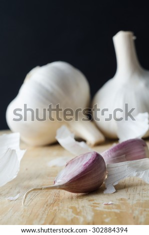 Two whole garlic bulbs in the background, with  pink cloves in foreground on a wooden chopping board surrounded by scattered fragments of shredded paper peelings  Close up (macro) image. - stock photo