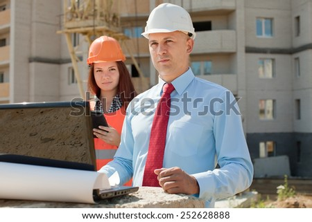 two workers wearing protective helmet works on the building site - stock photo