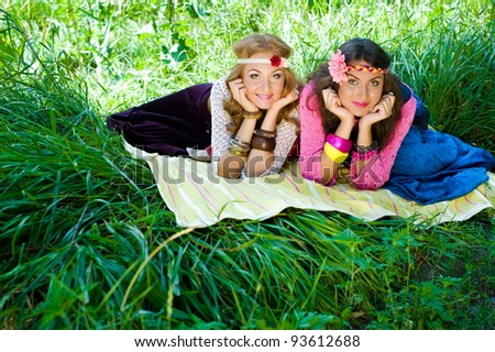 Two young beautiful girls lay on a grass in  a wood - stock photo