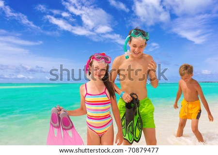 Two young bothers and sister playing in sea on tropical beach with sea and cloudscape background, Maldives.