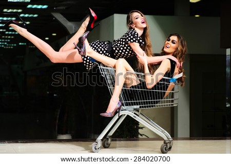 two young pretty sexual frolicsome girls with bright makeup and beautiful slim legs  short dress  jumped on shopping trolley with a girl sitting in it - stock photo