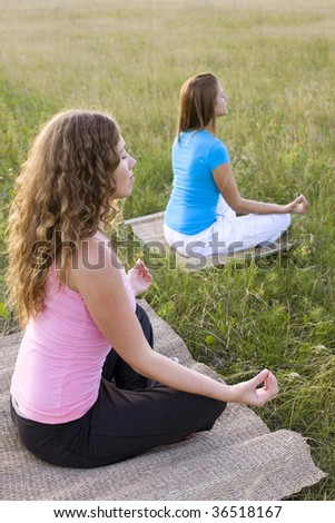 Two young woman doing yoga - stock photo