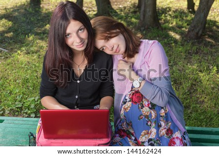 Two young women look a computer - stock photo