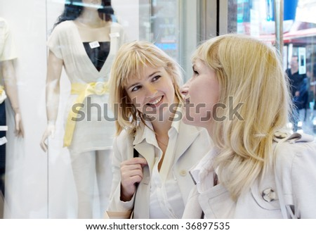 Two young women near a show-window of shop of clothes - stock photo
