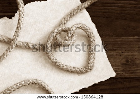"""Tying the knot' wedding invitation or save the date card in sepia tones. Rope knotted into a heart shape with hand torn parchment paper on rustic wood background. Macro with copy space.  - stock photo"