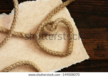 'Tying the knot' wedding invitation or save the date card.  Rope knotted into a heart shape with hand torn parchment paper on rustic wood background.  Macro with copy space. - stock photo