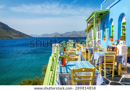 Typical Greek restaurant on the balcony blue building overlooking the sea, Greece - stock photo