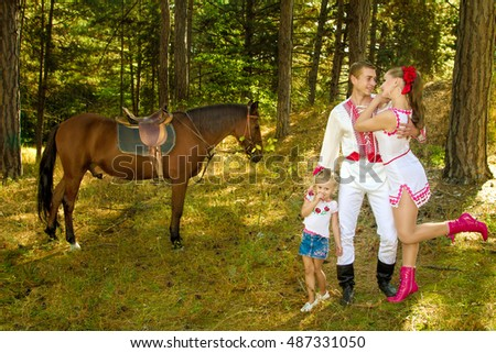 Ukrainians Mom and Dad and daughter in the woods with a horse