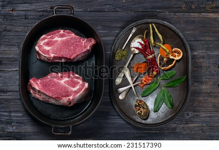 uncooked meat and assorted spices  on wooden background top view - stock photo
