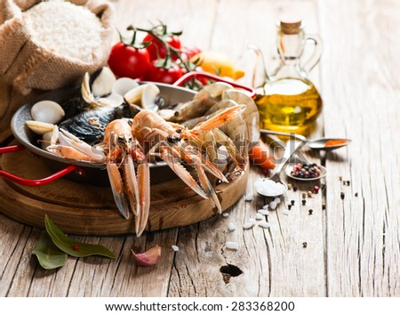Uncooked products of seafood paella on a wooden table  - stock photo