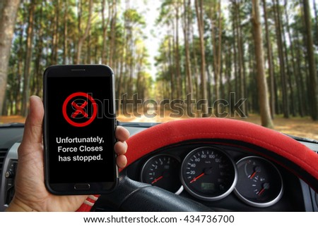 """""""Unfortunately, Force Closes has stopped"""" showing on the smartphone inside of a pickup truck. - stock photo"""