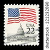 UNITED STATES - CIRCA 1985: A post stamp printed in the United States, features waving US flag and Capitol, circa 1985 - stock photo
