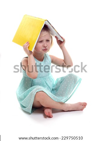 Unsatisfied blonde girl in dress 5 years sitting with an open book on her head. Isolated on white background - stock photo