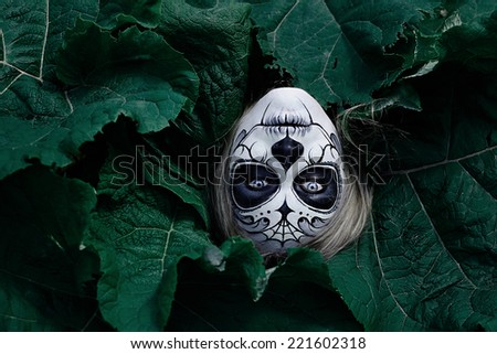 Upside Halloween Head/A head with a painted mask surrounded by burdock leaves, upside