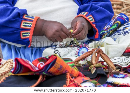 Uru woman from Titicaca lake creates traditional artwork of the Uru people  - stock photo