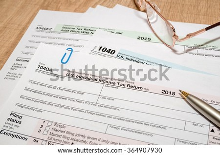 1040 US tax form for 2016 year with pen and glasses