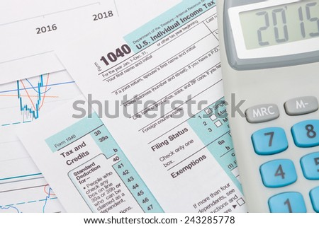1040 US Tax Form with calculator next to it - stock photo
