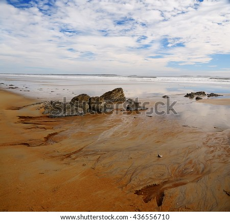 USA, Maine.  Atlantic ocean coast.Peaceful, soothing landscape of shoreline during low tide, the rocks on the beach and blue sky with clouds  - stock photo
