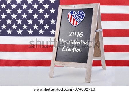 2016 USA presidential election notice board with heart shape vote badge on white wood surface with american stars and stripes flag in background.