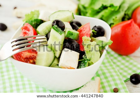 useful dietary breakfast or lunch , Greek salad with fresh vegetables , tomatoes, cucumbers , lettuce, black olives , feta cheese and white toast on a wooden background