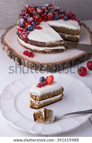 ?ut a piece of Earl Grey cake with cream cheese and berries and mashed strawberries in brandy inside, on white plate with strawberry, red currant and blueberry - stock photo