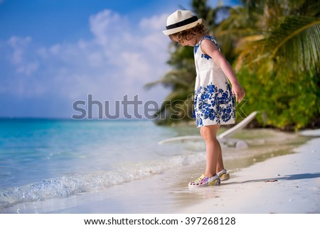 ?ute little girl in beautiful dress and hat playing with sand on the tropical beach with white sand, azure blue sea and coconut palms. Paradise Landscape background.   - stock photo
