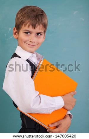��¡ute schoolboy is holding an orange book against school blackboard - stock photo