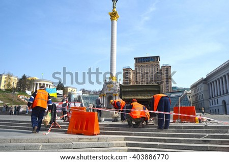 : Utility workers in orange vests repair after riot and vandalism 2013-2014. Khreshatik - central street of Kiev.At April 8,2016 in Kiev, Ukraine - stock photo