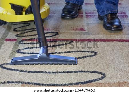vacuum men cleaner a carpet - stock photo